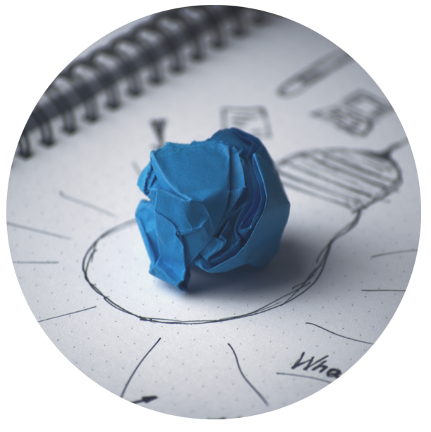 Crumpled blue paper on a drawing of a light bulb.